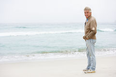 Senior Man On Holiday Standing On Winter Beach. At Camera Royalty Free Stock Photo
