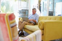 Senior Man At Home In Lounge Using Laptop Computer Royalty Free Stock Image