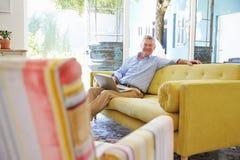 Senior Man At Home In Lounge Using Laptop Computer Royalty Free Stock Photos