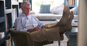 Senior Man In Home Office Doing Paperwork With Feet On Desk stock footage