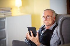 Senior man at home reading on a e-book 6 Stock Photography