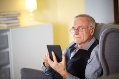 Senior man at home reading on a e-book 4 Stock Image