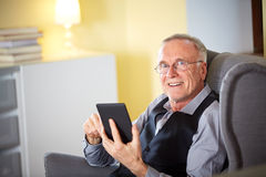 Senior man at home reading on a e-book Stock Image