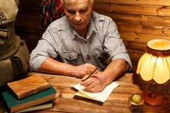 Senior man in homely interior. Senior writing letter with quill pen in homely wooden interior royalty free stock image