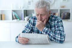 Senior man at homesenior man reading newspaper at home stock photo