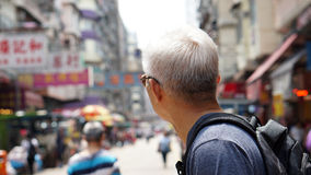 Senior man with hong kong urban architecture scene. Travel to experience different place stock photos