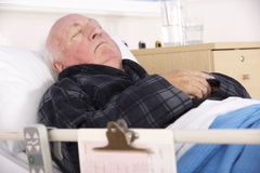 Senior man in hospital bed Stock Photo