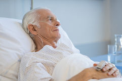 Senior man hospitalized. Sad senior man lying on hospital bed and looking away. Old patient with oxygen tube feeling lonely and thinking at hospital. Sick aged Stock Images