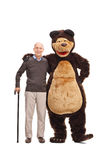 Senior man hugging a guy in bear costume Royalty Free Stock Images