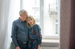 Senior Man Hugging His Young Blond Wife near the Window. Woman Looking at the Camera. Psychology of Relations Concept. Senior Man Hugging His Young Blond Wife stock photos