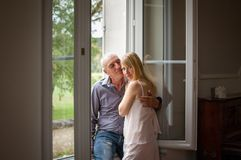 Senior Man Hugging His Young Blond Wife near the Window. Woman Looking at the Camera. Psychology of Relations Concept. Senior Man Hugging His Young Blond Wife royalty free stock photo