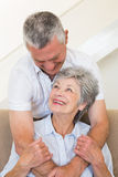 Senior man hugging wife sitting on sofa Stock Photography