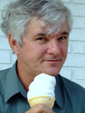 Senior Man with Ice Cream Cone. Handsome middle-aged man enjoying a sweet treat Royalty Free Stock Photography