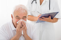 Senior Man Infected With Cold Blowing His Nose In Clinic. Senior Man Infected With Cold Blowing His Nose While Doctor Writing On Clipboard In Clinic Royalty Free Stock Images