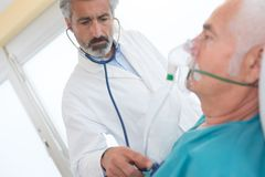 Senior man inhaling through oxygen mask in clinic. Senior men inhaling through oxygen mask in clinic man royalty free stock photo