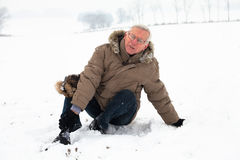Senior man with injured leg on snow Stock Image