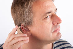 Senior man inserting a hearing aid Stock Image