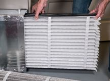 Senior man inserting a new air filter in a HVAC Furnace. Senior caucasian man changing a folded air filter in the HVAC furnace system in basement of home stock photos