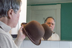Senior man inspecting his brown derby in the bathroom mirror Royalty Free Stock Images