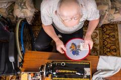 Senior Man Inspecting Needlepoint Work Stock Images