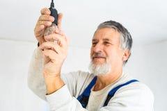 Senior man installing a bulb Royalty Free Stock Image