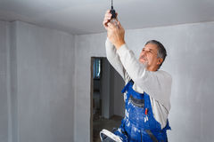 Senior man installing a bulb in a freshly renovated appartment i Stock Images