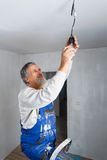Senior man installing a bulb in a freshly renovated appartment i Royalty Free Stock Photo