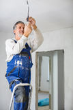Senior man installing a bulb in a freshly renovated appartment i Stock Image