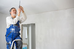 Senior man installing a bulb in a freshly renovated appartment i Stock Photos