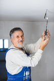 Senior man installing a bulb in a freshly renovated appartment i Royalty Free Stock Photography