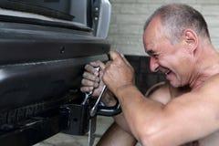 Senior man installing hitch car Stock Image