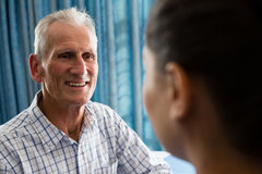 Senior man interactin with female doctor in retirement home. Happy senior men interactin with female doctor in retirement home Royalty Free Stock Image
