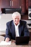 Senior man internet banking. Senior man doing internet banking at home and looks worried royalty free stock image