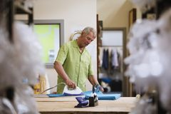 Senior Man Ironing Fabric Royalty Free Stock Photos