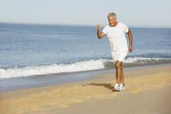 Senior Man Jogging Along Beach Royalty Free Stock Photos