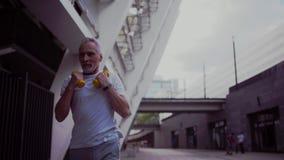 Senior man jogging with dumbbells. stock footage