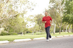 Senior Man Jogging In Park Stock Photo