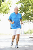 Senior Man Jogging In Park. Smiling stock photos