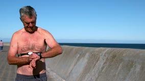 Senior man jogging shirtless on sunny day stock video