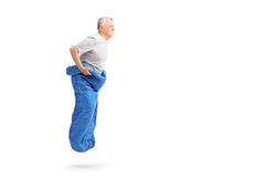 Senior man jumping in a blue sack and smiling Royalty Free Stock Image