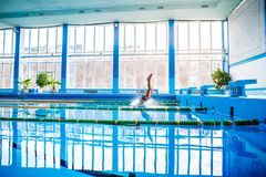 Senior man jumping in the swimming pool. Senior man in an indoor swimming pool. Active pensioner enjoying sport. An old man jumping in the pool Stock Photos