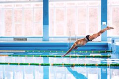 Senior man jumping in the swimming pool. Senior man in an indoor swimming pool. Active pensioner enjoying sport. An old man jumping in the pool Stock Photography
