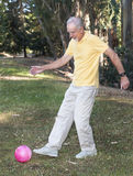 Senior man kicking ball in park Stock Images
