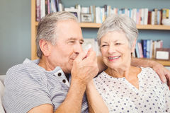 Senior man kissing his wife hand while sitting at home Royalty Free Stock Photo