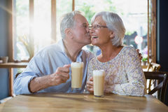 Senior man kissing senior woman. In caf Royalty Free Stock Images