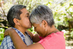 Senior man kissing woman on forehead in garden Stock Images