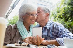 Senior man kissing woman. In outdoor caf Royalty Free Stock Images