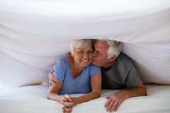 Senior man kissing woman under blanket on bed. In bedroom Royalty Free Stock Photography