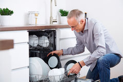 Senior man in the kitchen 5. Senior man in the kitchen, empty out the dishwasher Stock Photos