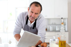 Senior man in the kitchen looking for recipe Stock Image